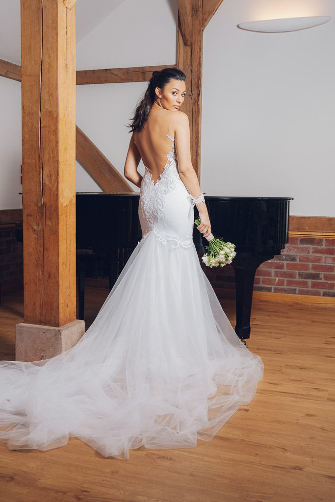 Bride stands by grand piano