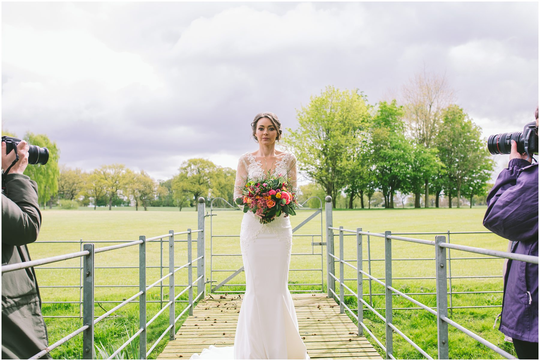 The bride holds her flowers as two photographers create images