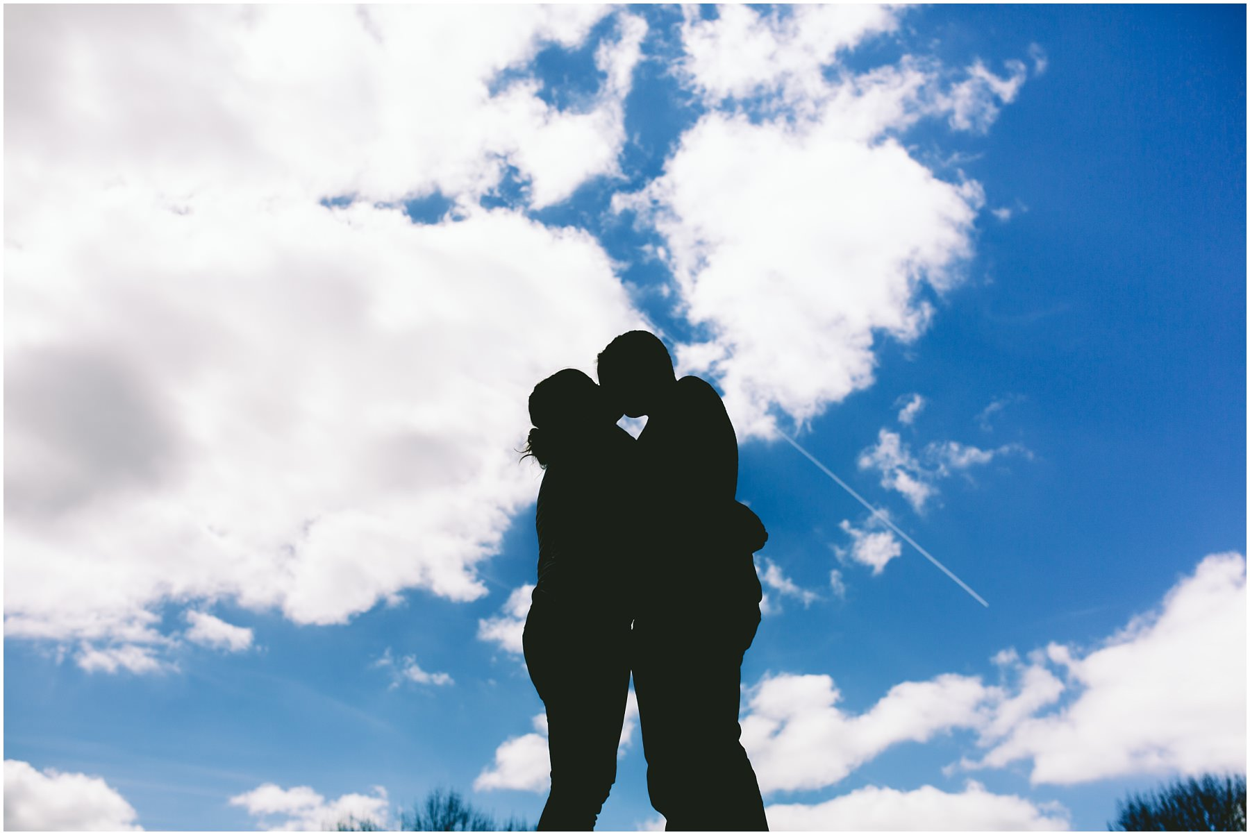 A couple silhouetted against a cloudy sky.