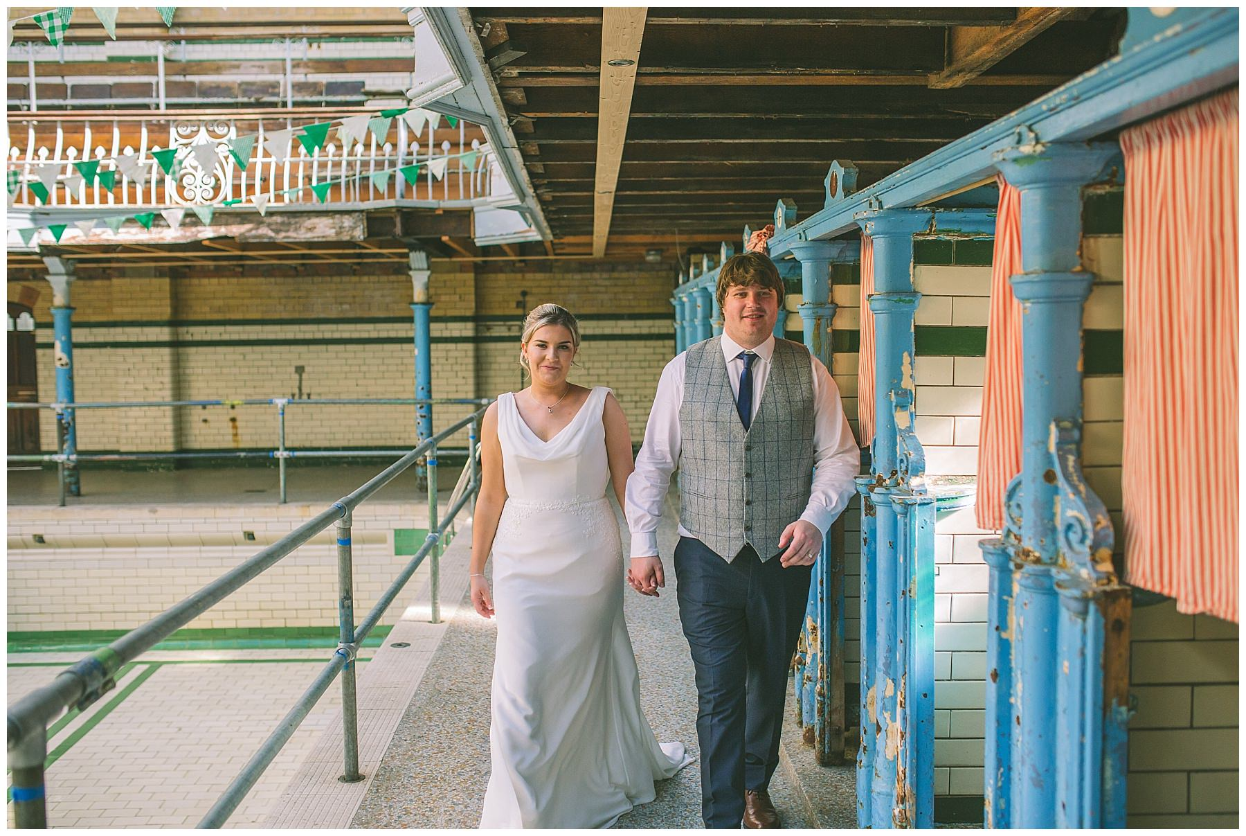 Bride and Groom walk down the poolside at Victoria Baths