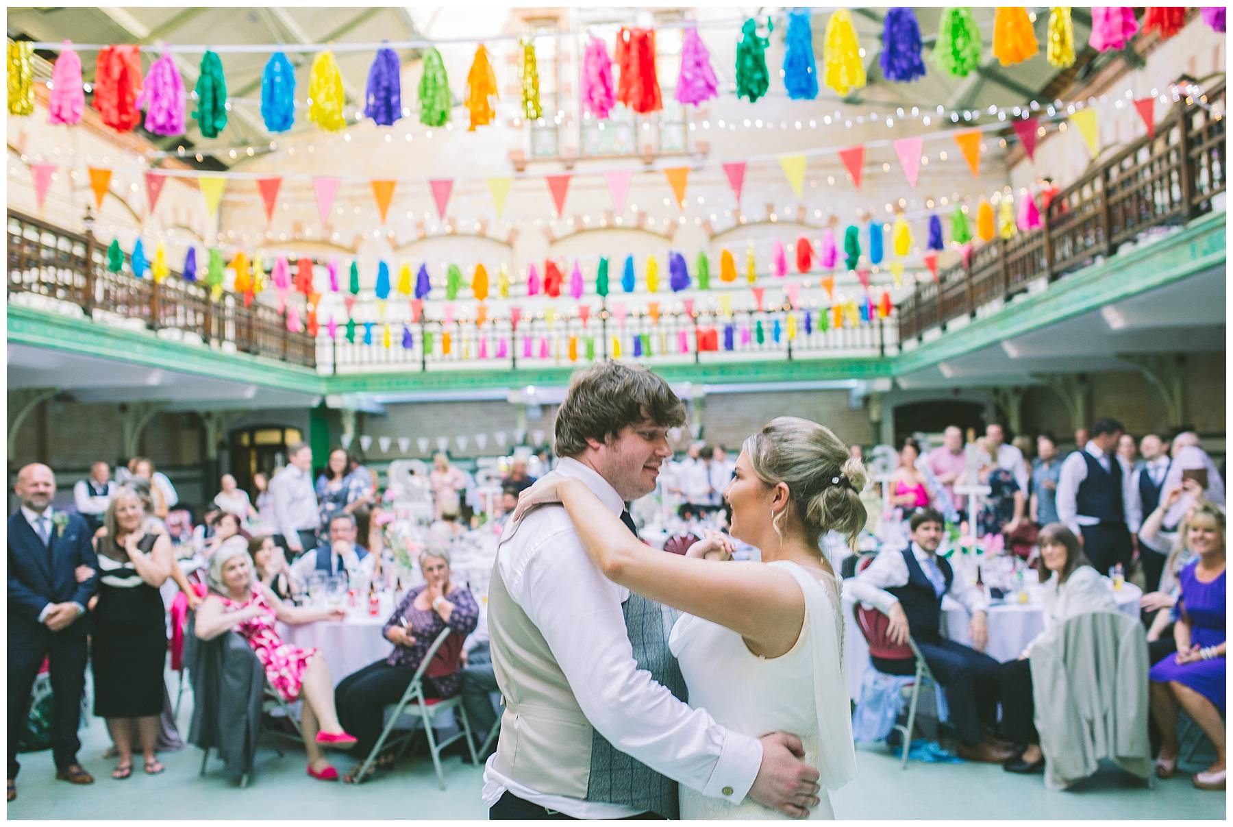 Bride and Groom dance in front of friends and family