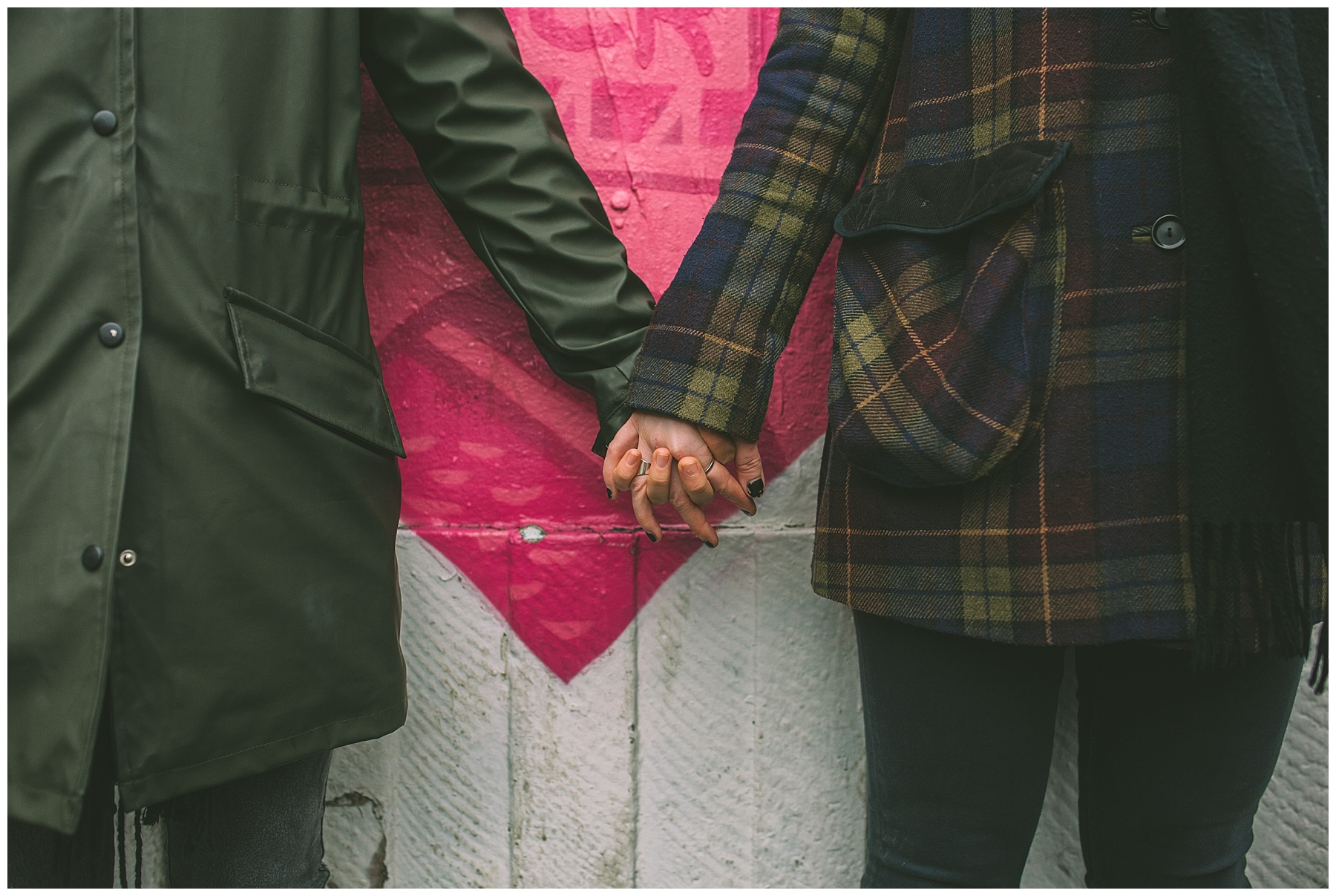 Couple hold hands in front of hear shaped graffiti in Manchester