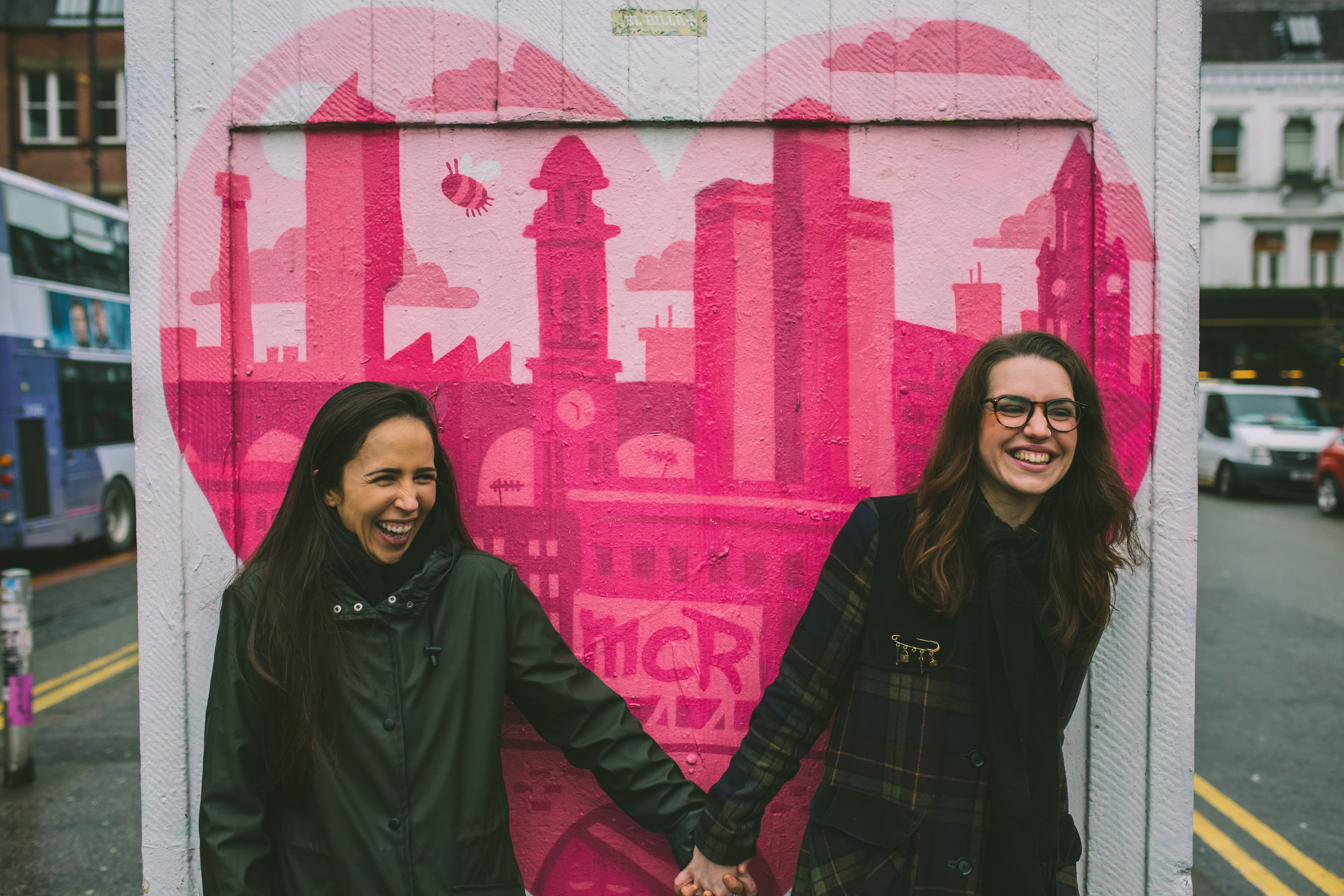 Female couple laugh holding hands in front of Manchester graffiti