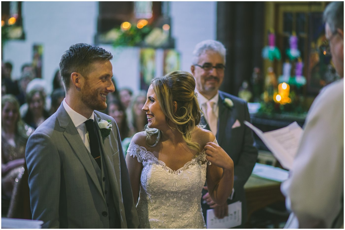 bride and groom share a smile during the service