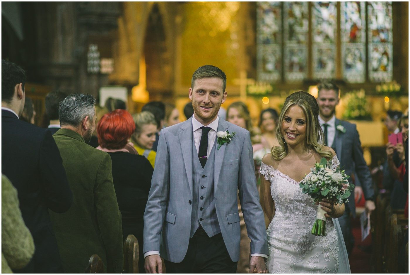 bride and groom smile as they exit the church as newly weds