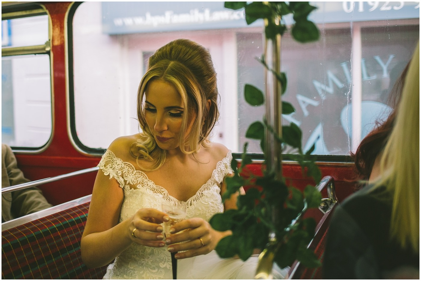 Bride enjoys a glass of prosecco on vintage bus