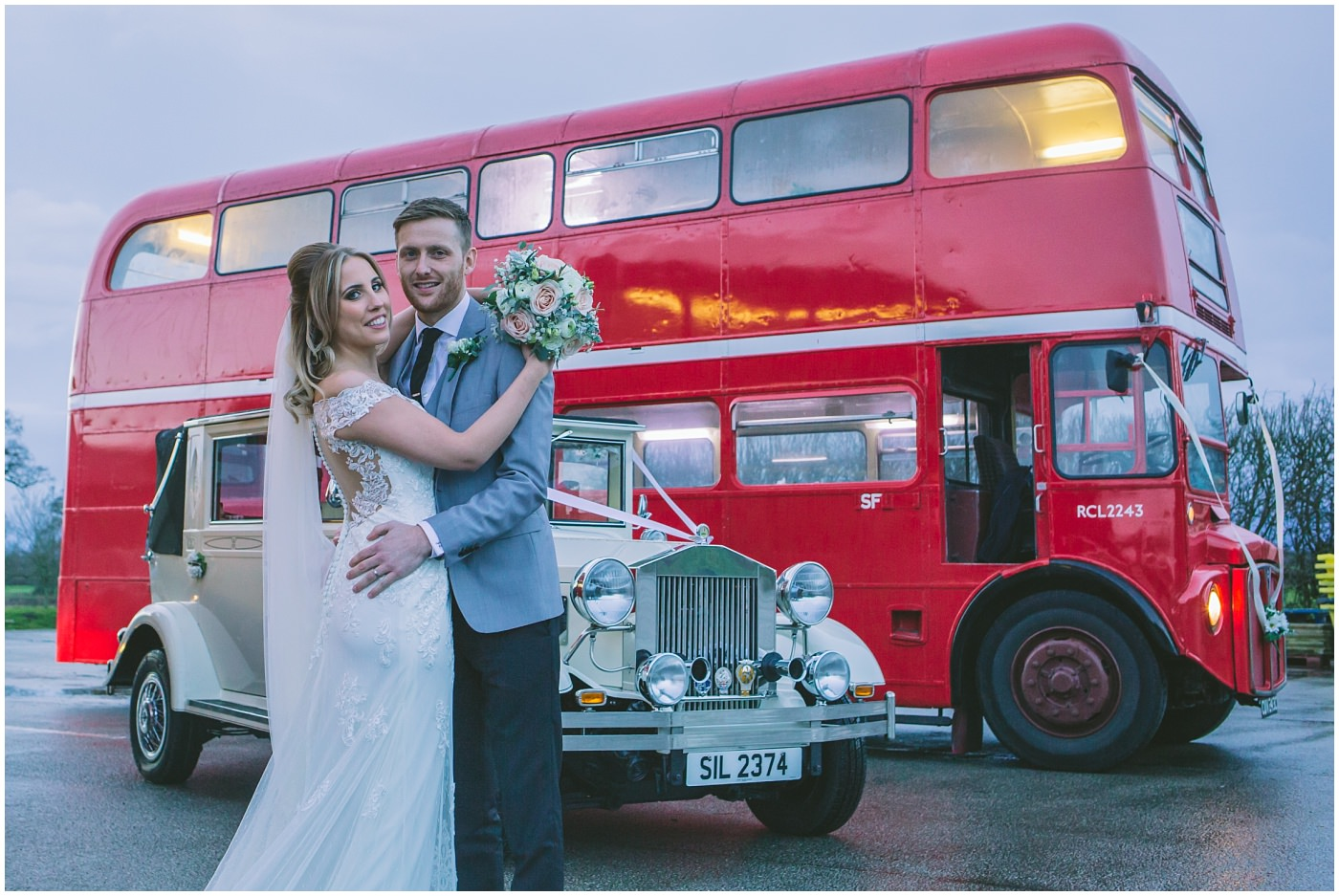 Bride and Groom pose in front of vintage wedding transport