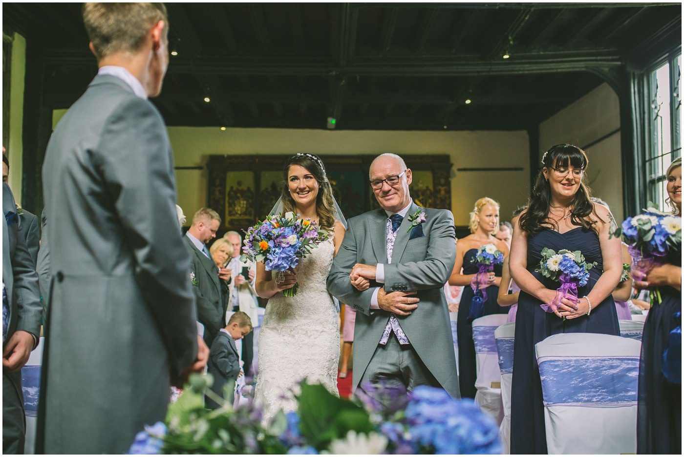 Bride smiles as she is walked down the isle by her dad