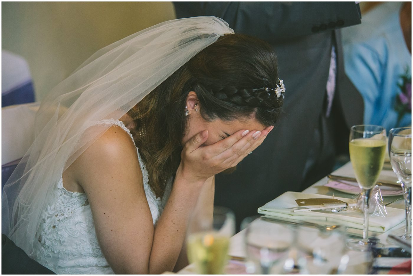 bride hides her face in her hands during an embarrassing speech by dad