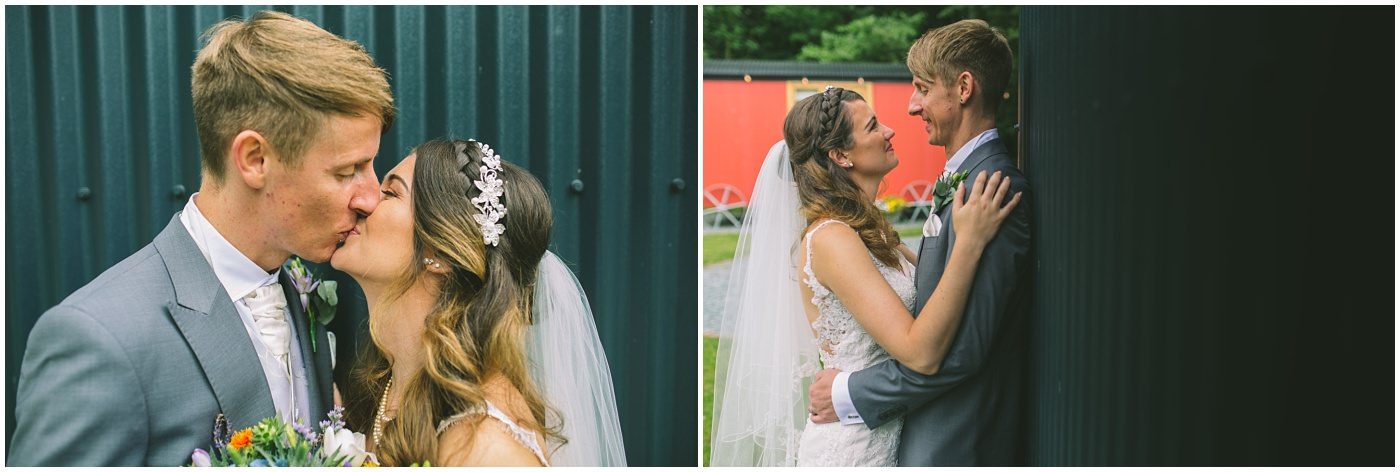 married couple share a kiss by the shepherds huts at samlesbury hall