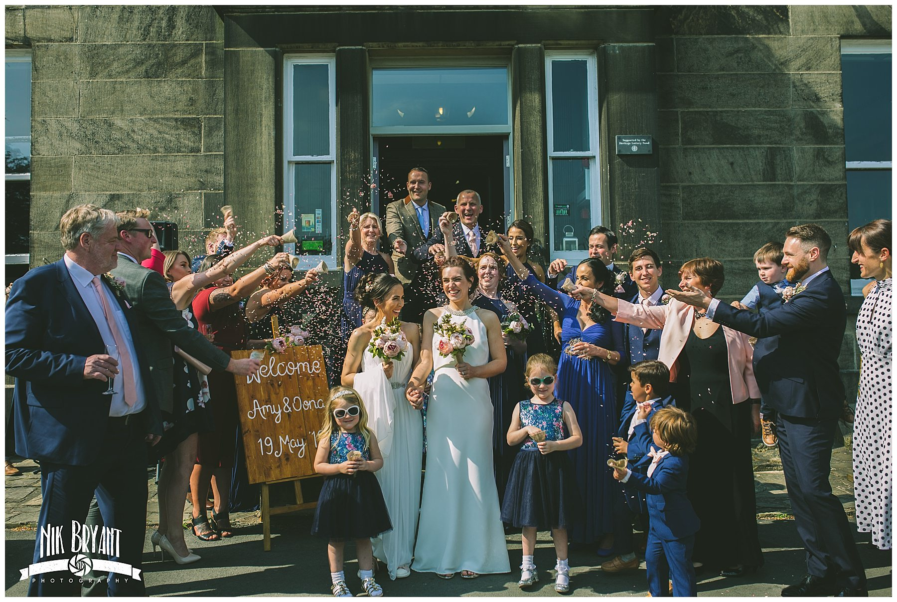 two brides showered in confetti by friends and family