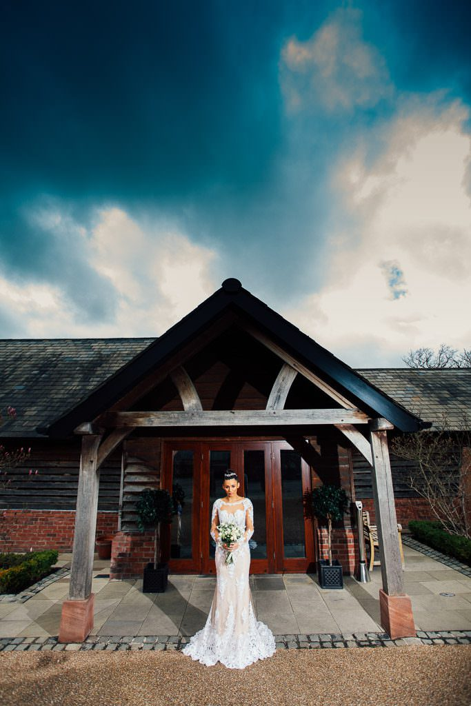 Bride wearing Riki Dalal Dress from The White Gallery Ramsbottom outside Sandhole Oak Barn