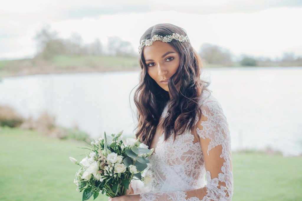 Bride looks to camera whilst holding bouquet