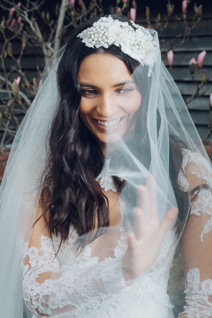 Bride laughing and smiling whilst playing with veil