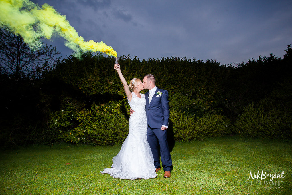 Bride and groom kiss with smoke grenade