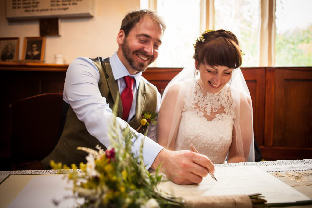 A couple laugh as they sign the wedding register