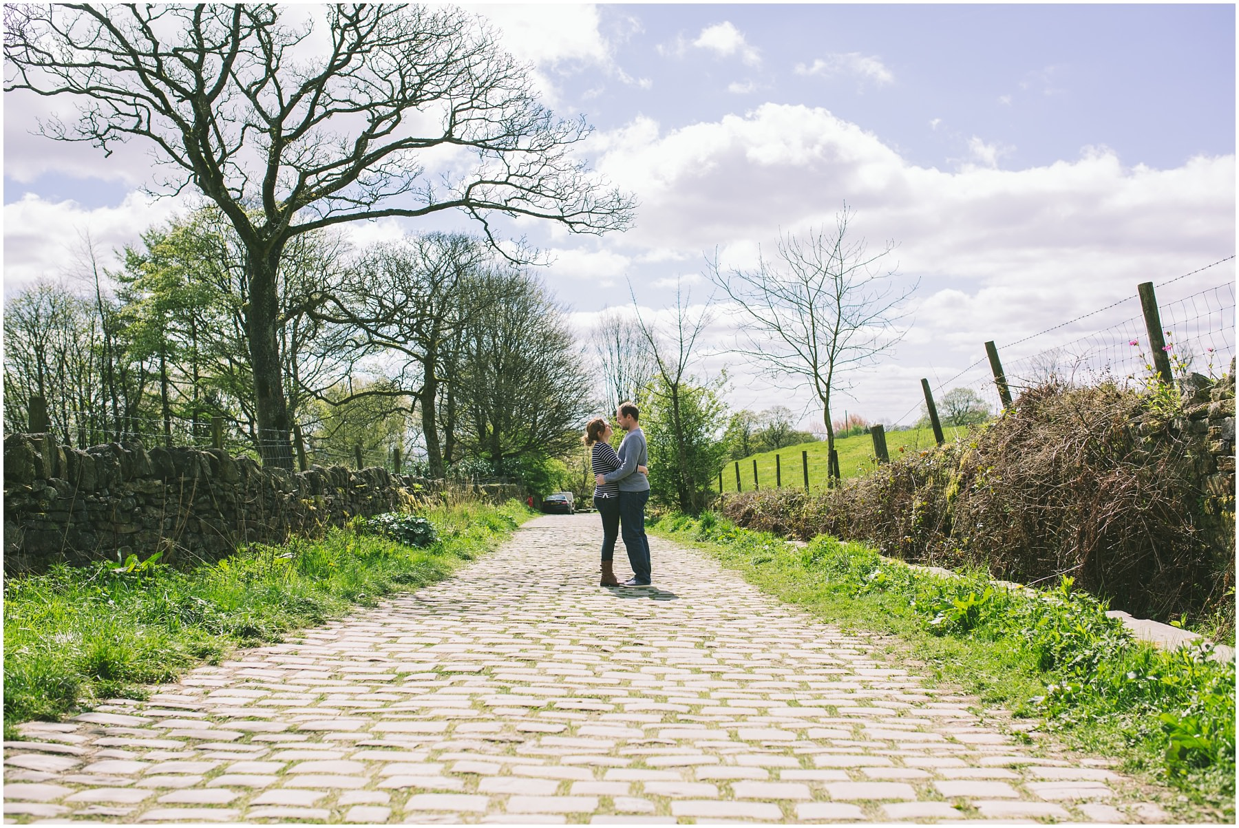 a couple stand on a cobbled lane and embrace