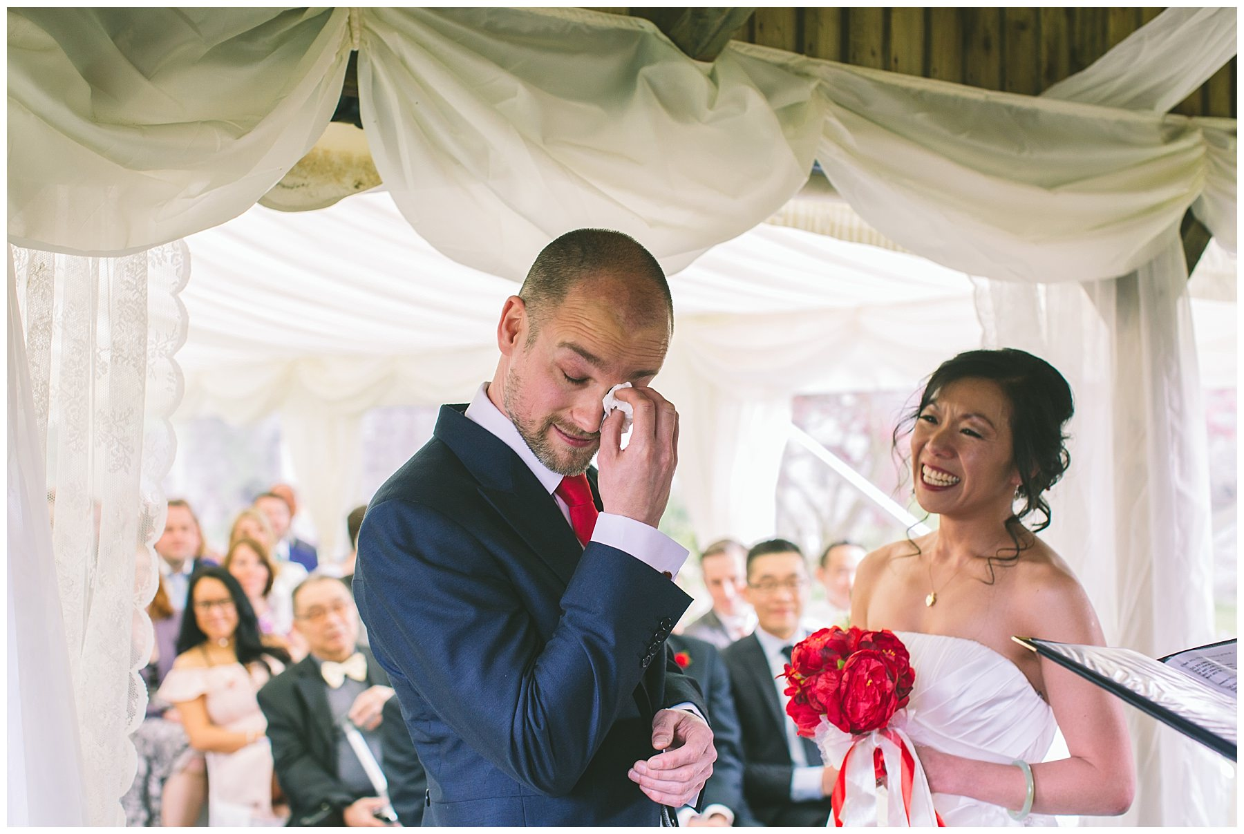 Groom wipes away a tear during wedding ceremony