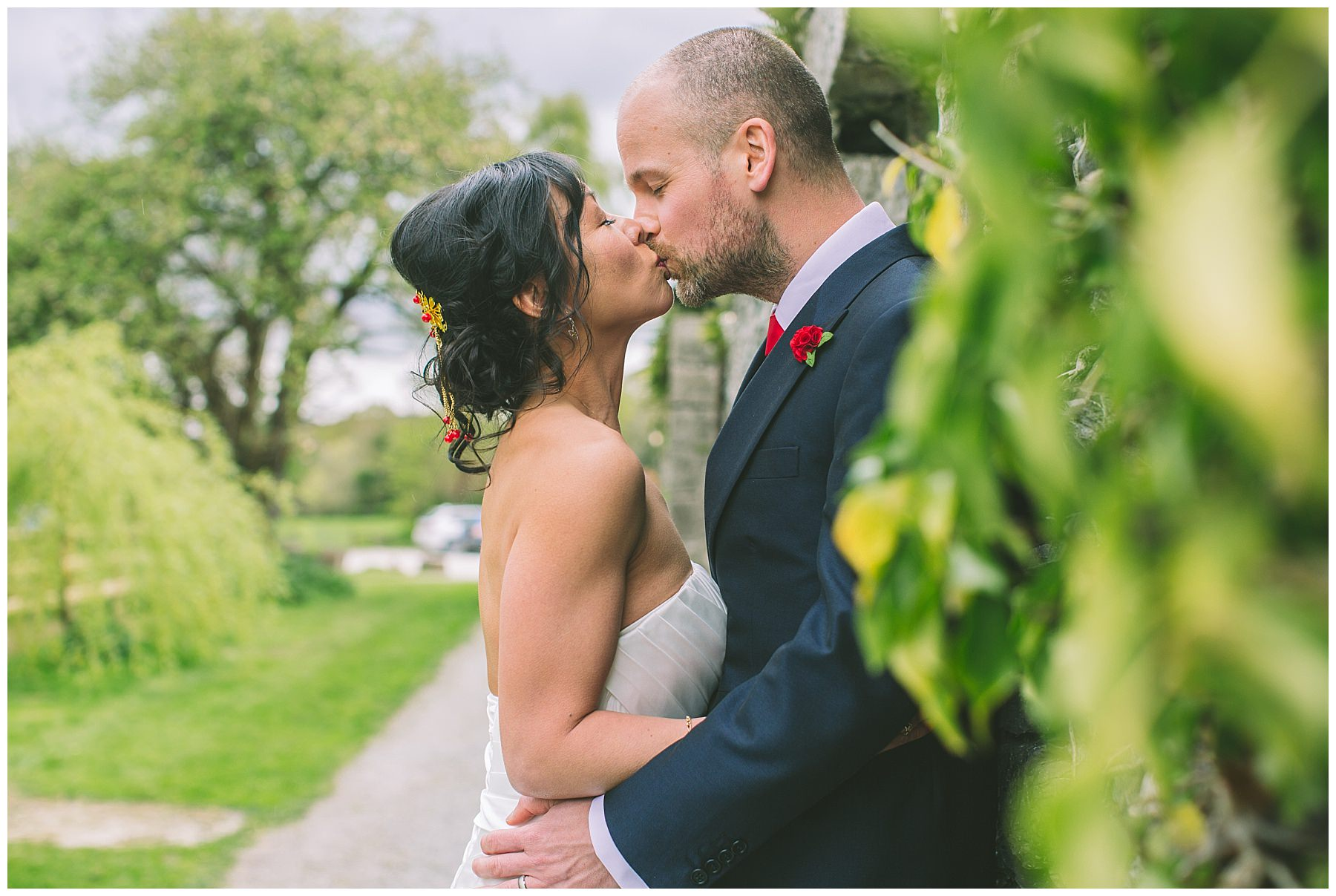 Newlyweds share a kiss amongst the Ivy