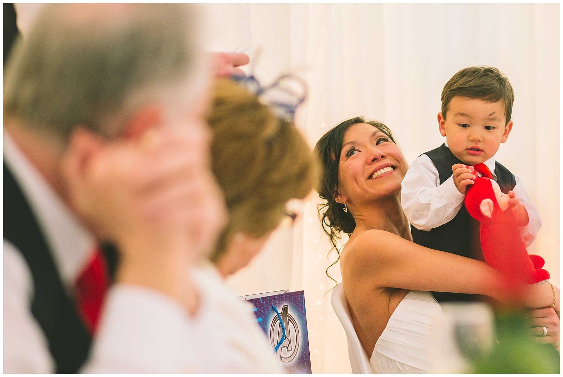 Bride looks on and smiles during speeches