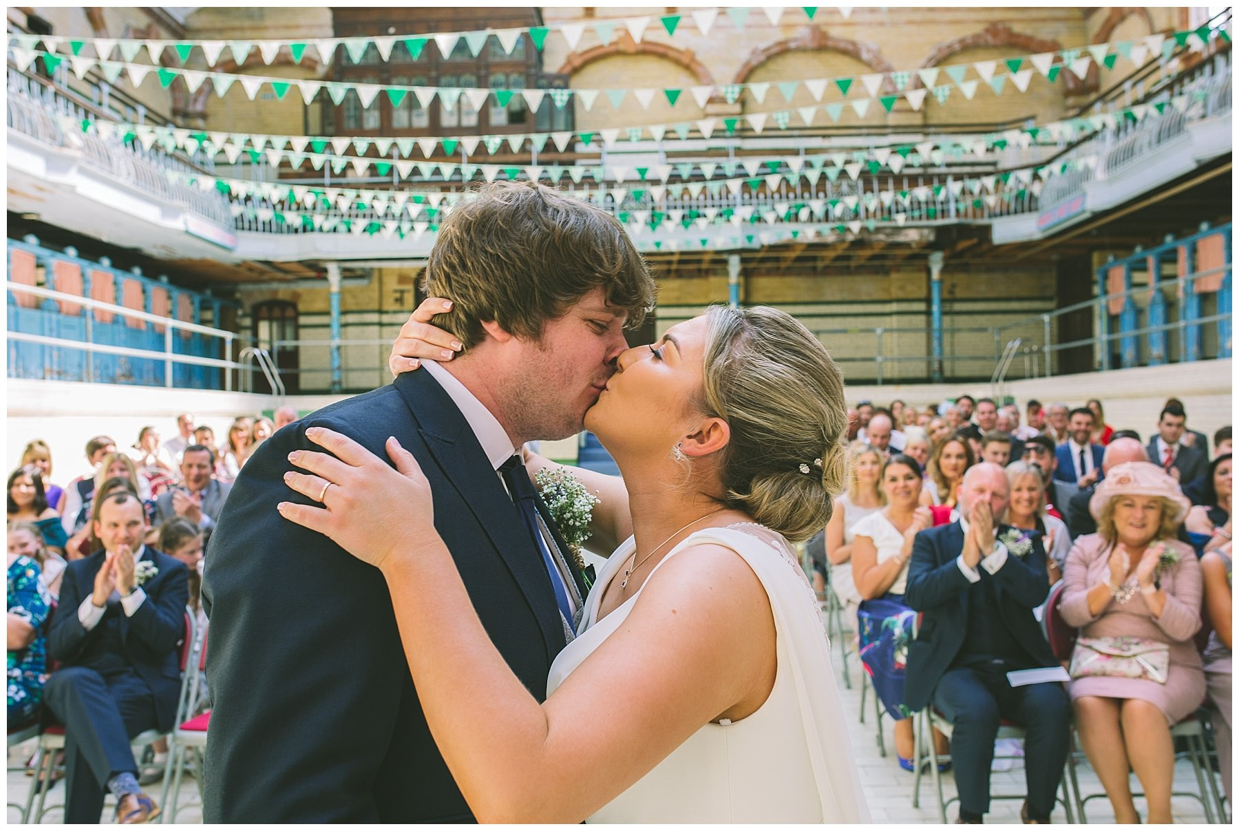 First kiss under the bunting in the pool at Victoria Baths