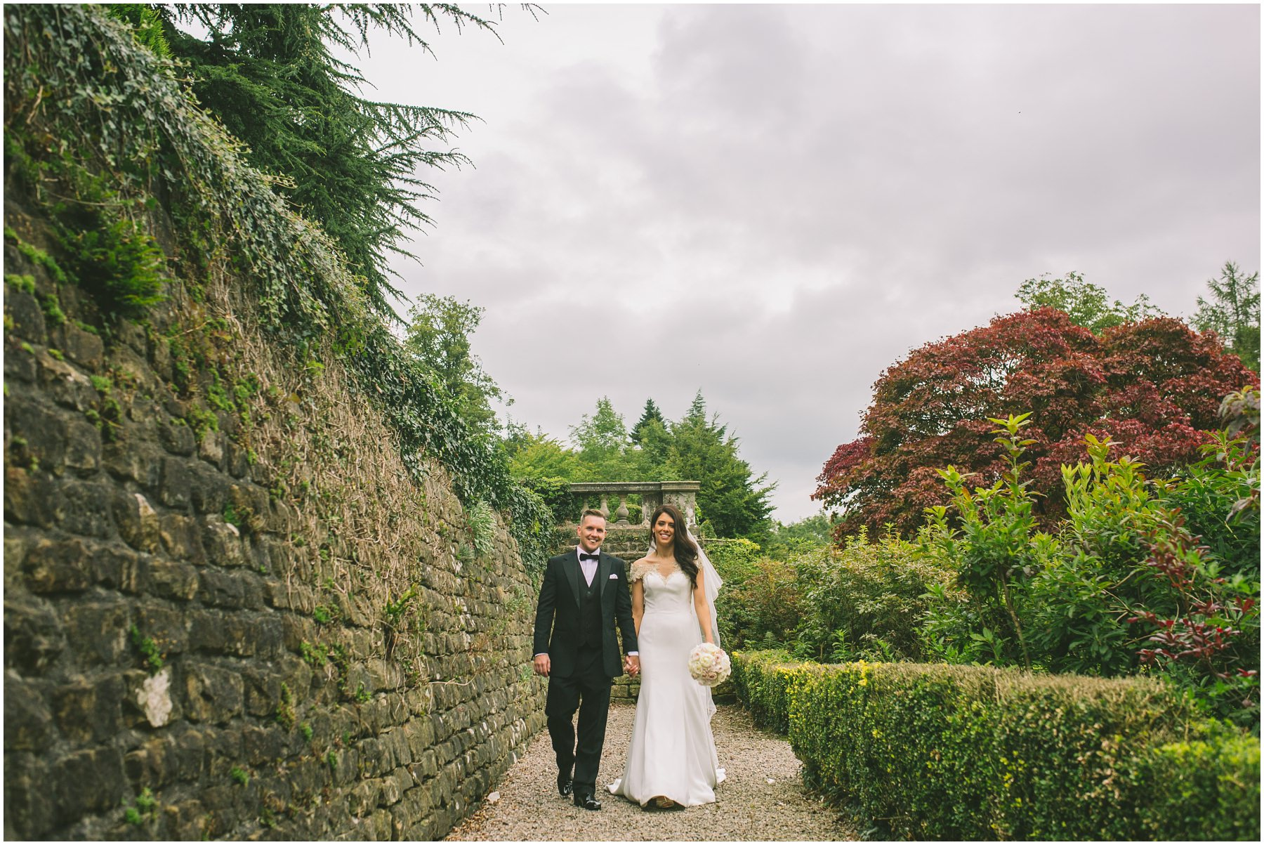 married couple walk through the gardens at Eaves Hall