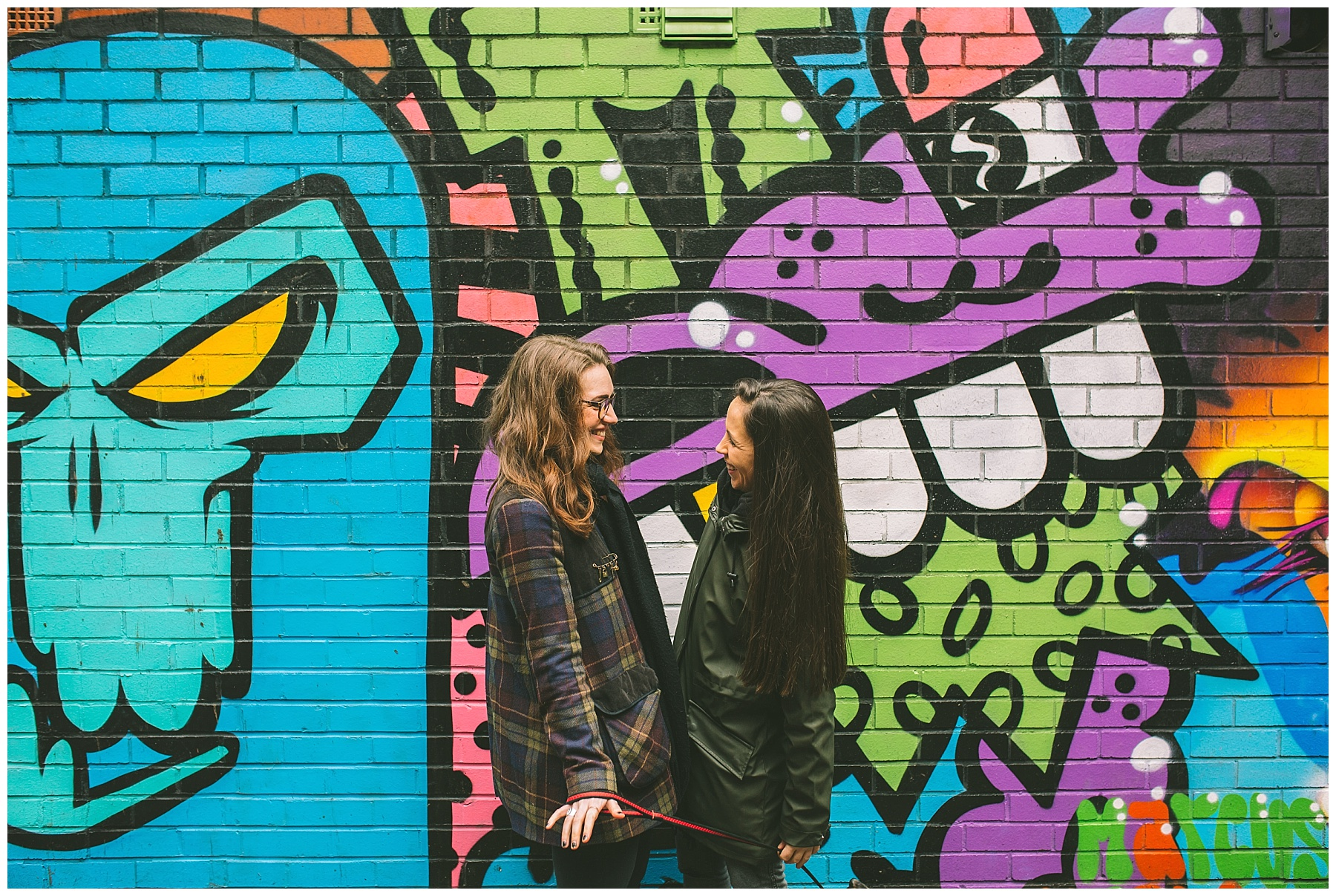 Same sex couple stand in front of a graffiti mural