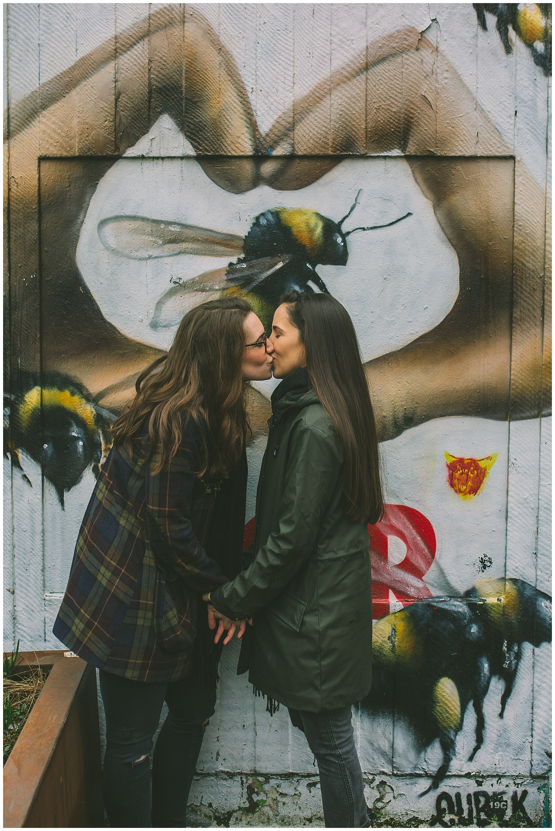 Couple share a kiss in front of iconic Manchester bee graffiti