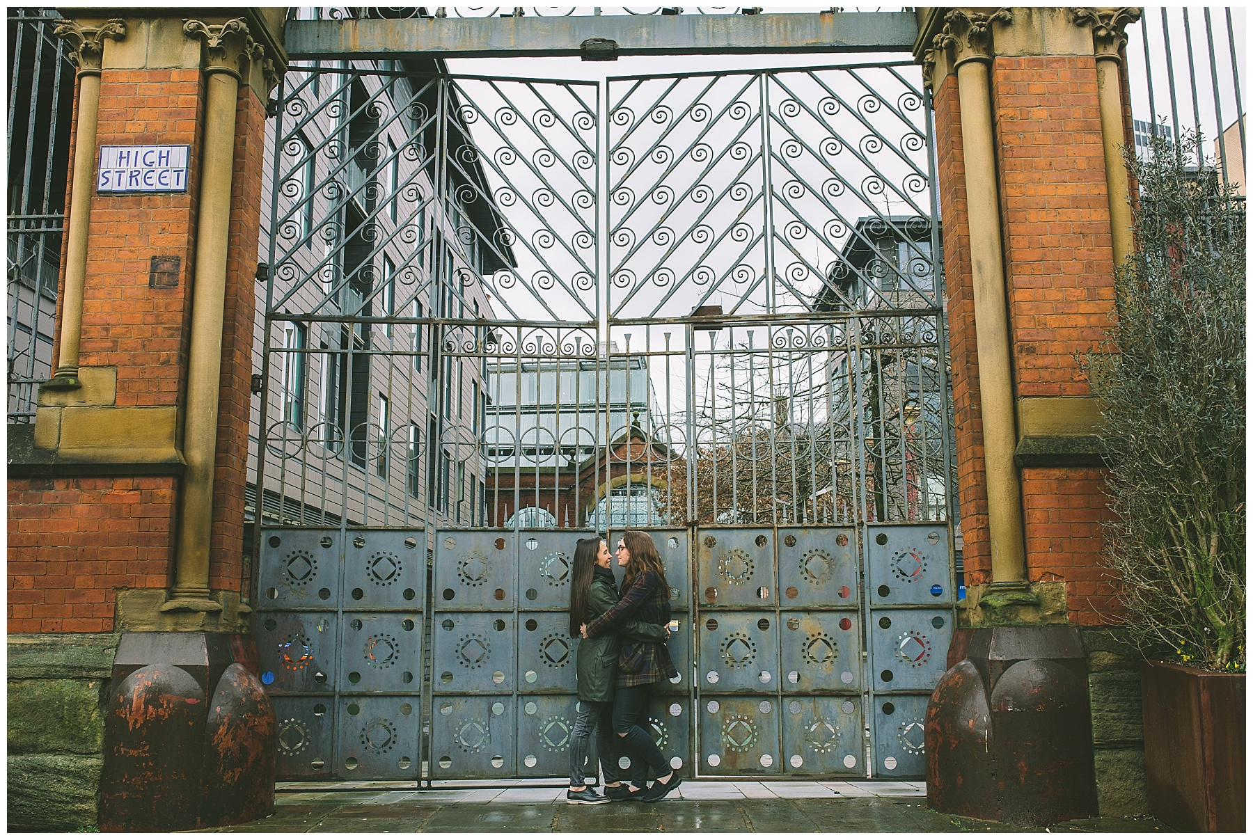 lesbian couple share a moment in front of the gates of the old Manchester fish markets