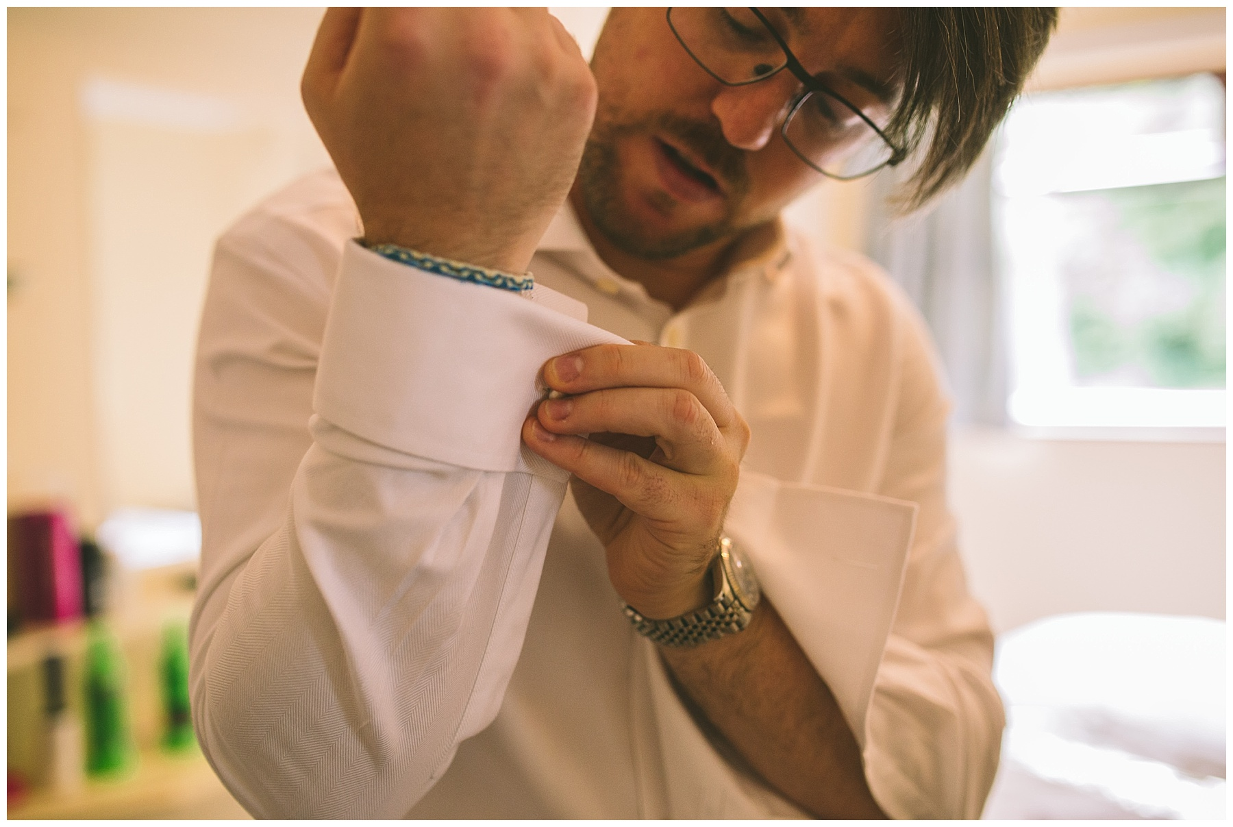 Groom puts on his cufflinks