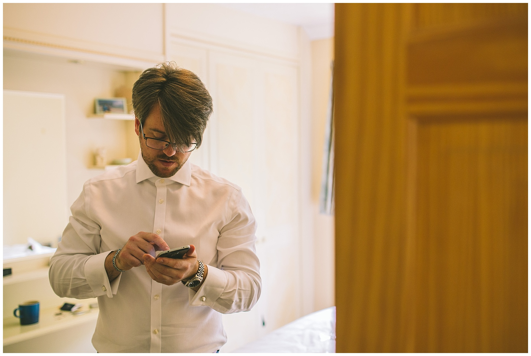 groom checks his phone on the wedding morning