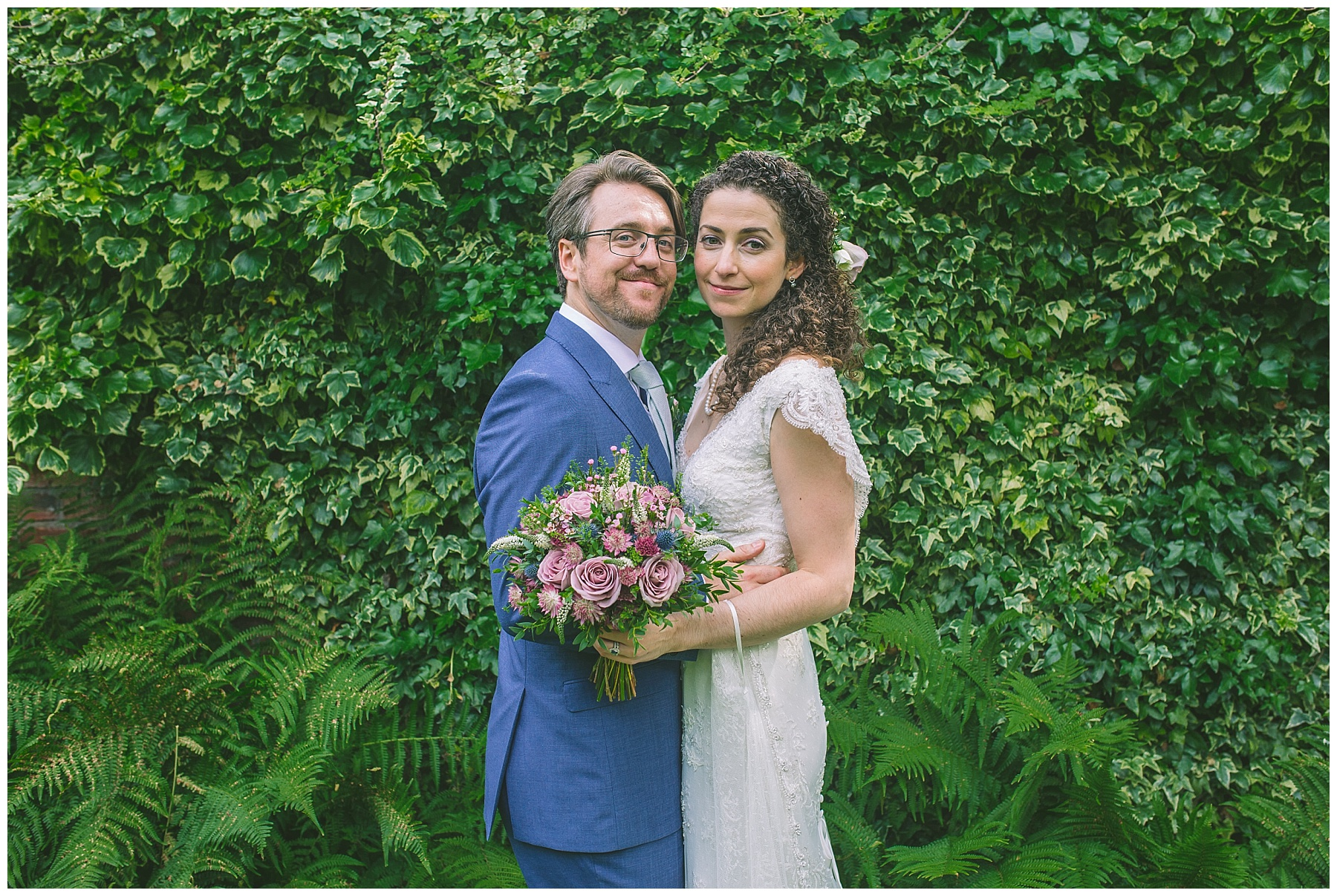 married couple in front of all the greenery in the gardens of Eleven Didsbury Park