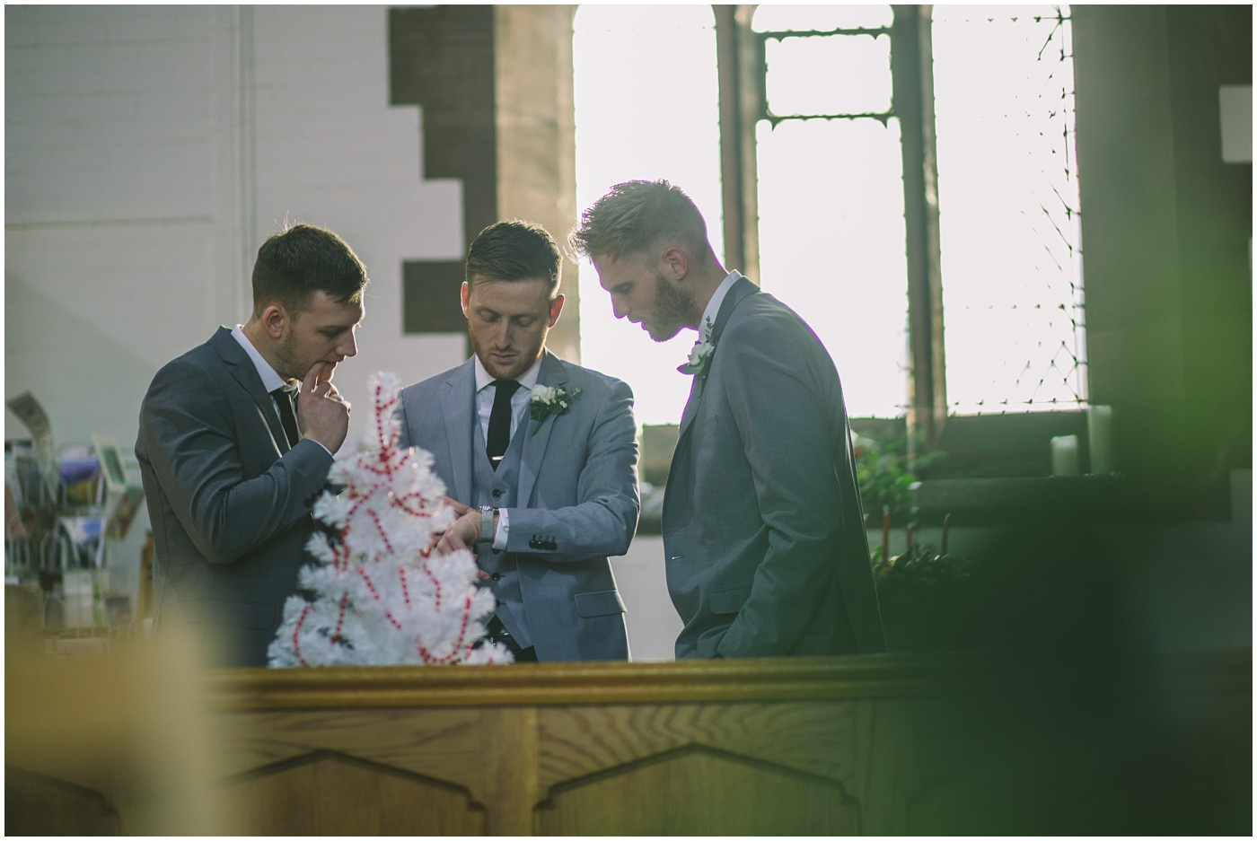 Groom checks his watch at church as he waits for his bride
