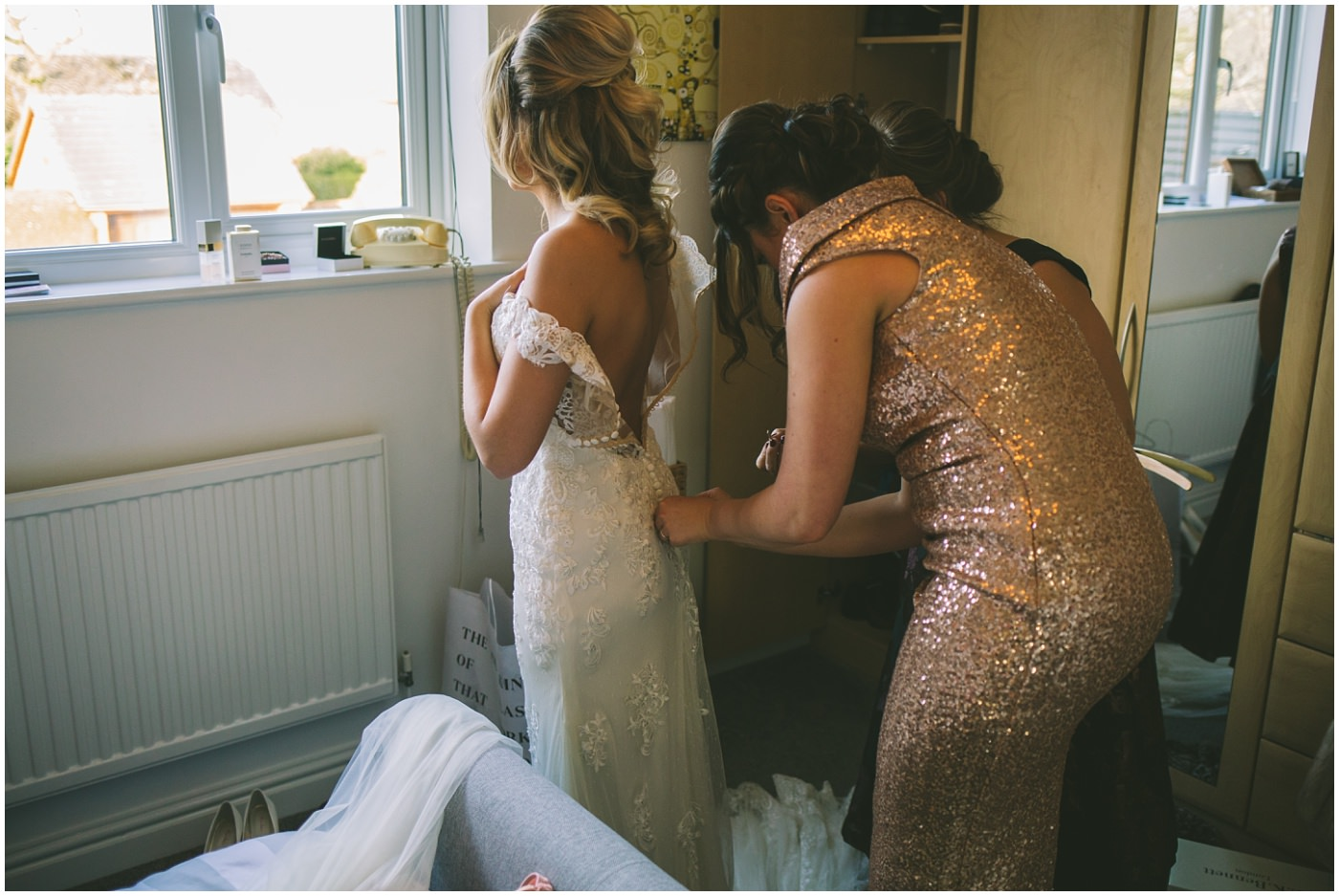 bridesmaids assist becca into her wedding dress for her pryors hayes wedding