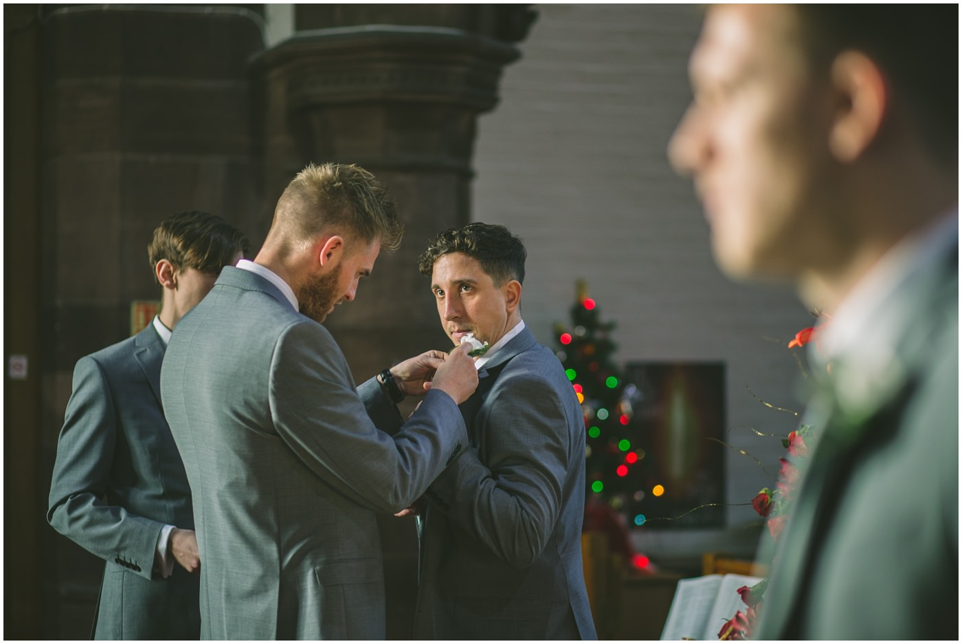 best man applies buttonhole for groomsman