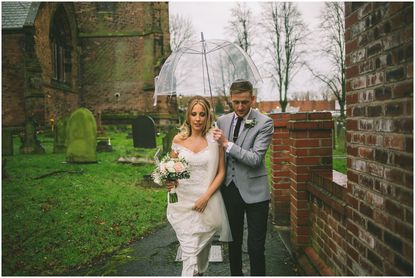 Groom holds umbrella over his bride as they exit the church