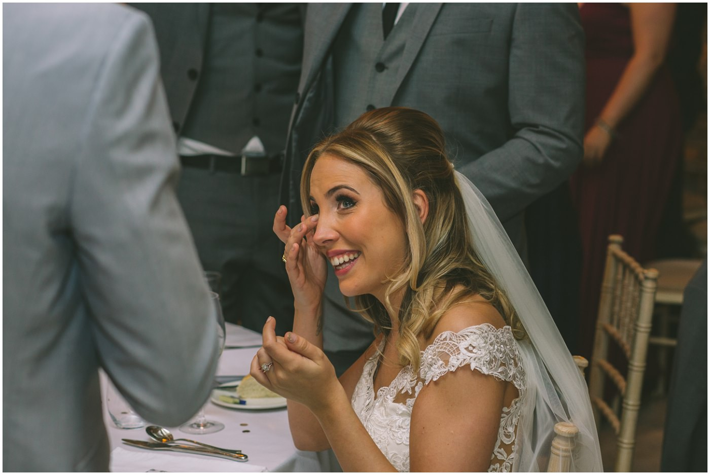 bride wipes away a tear during her husbands speech