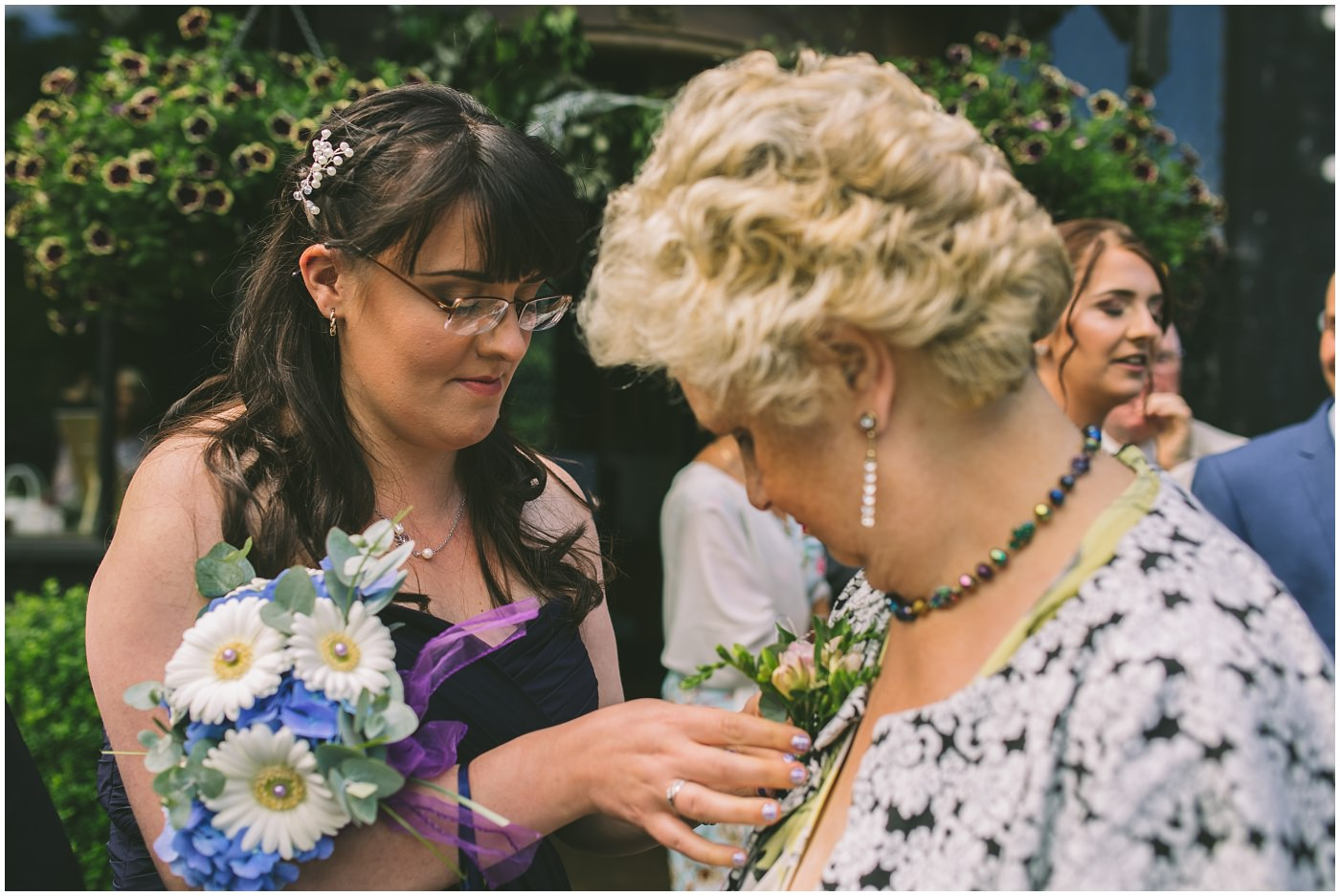 button hole being applied by a bridesmaid