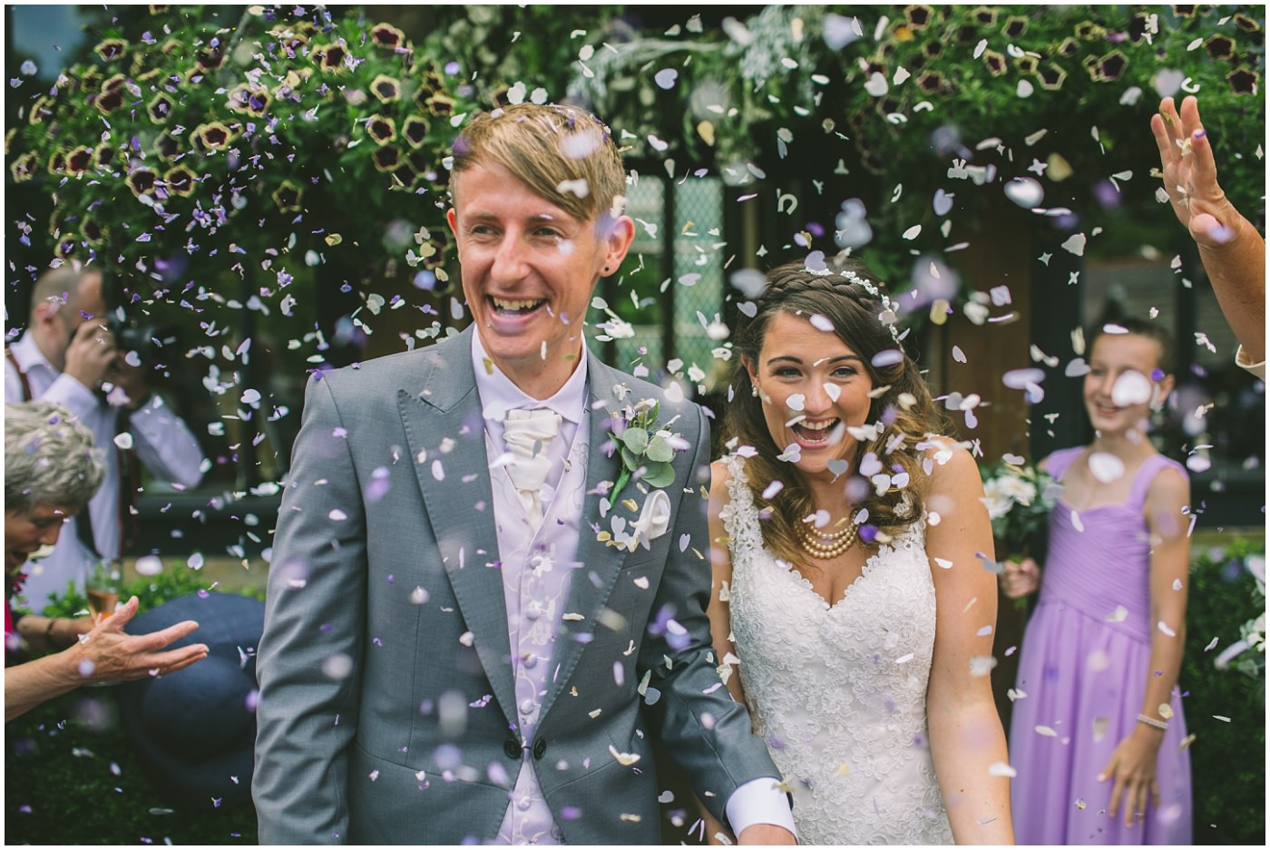 masses of confetti shower the bride and groom