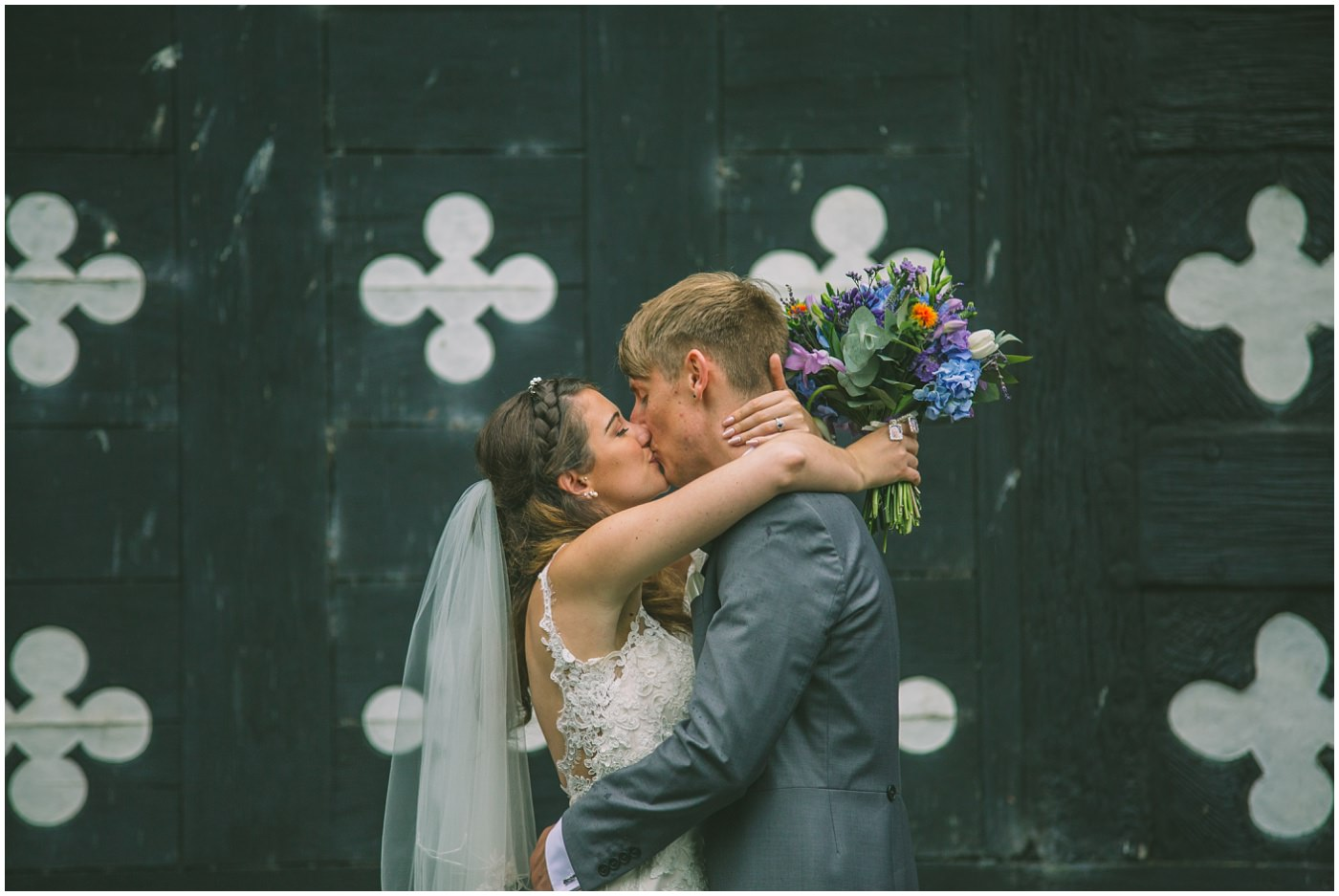 married couple kiss outside the iconic walls at samlesbury