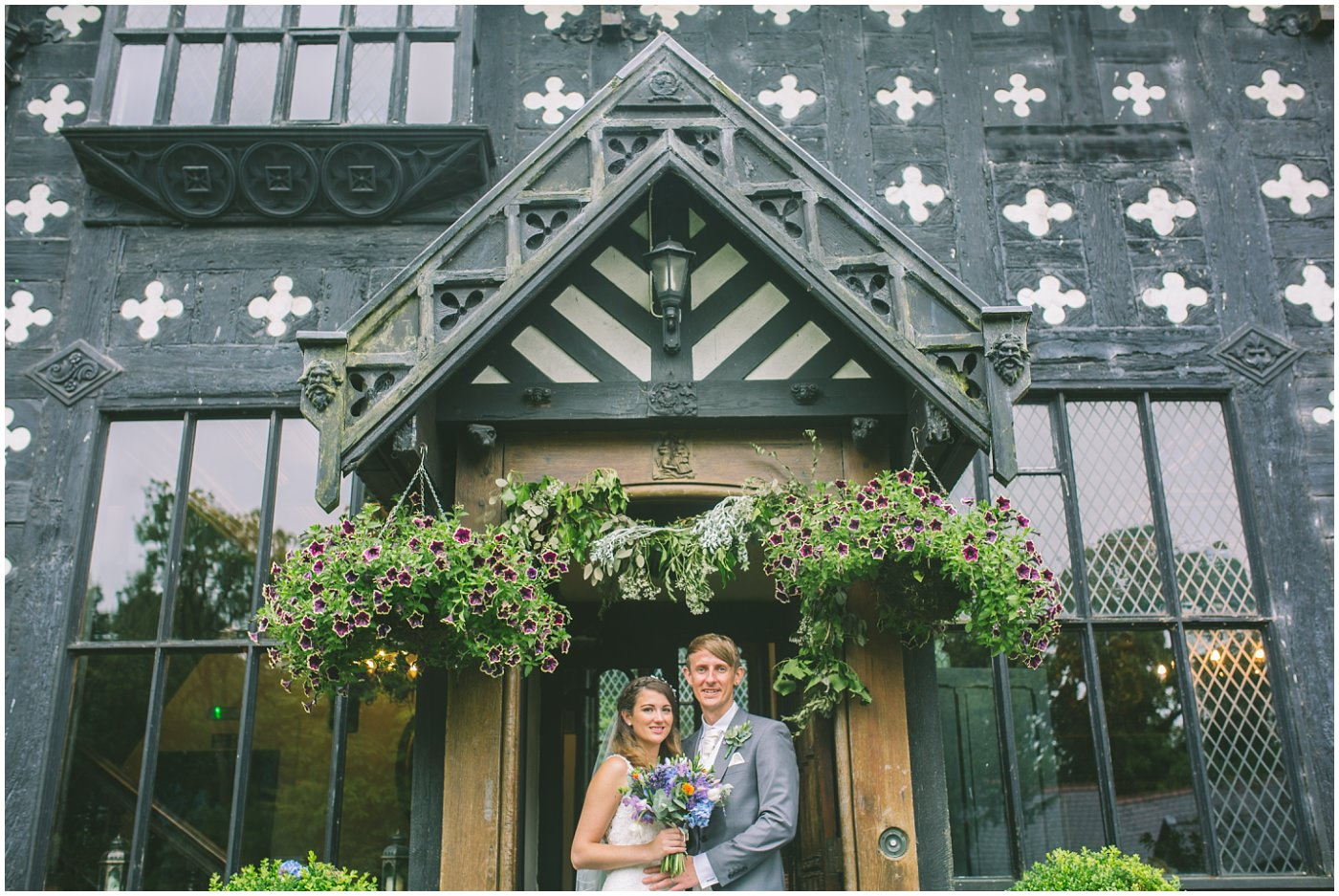 Newly married couple stand for portraits outside the front of Samlesbury Hall