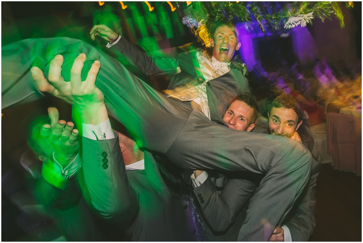 groom lifted up on the dancefloor by his groomsmen