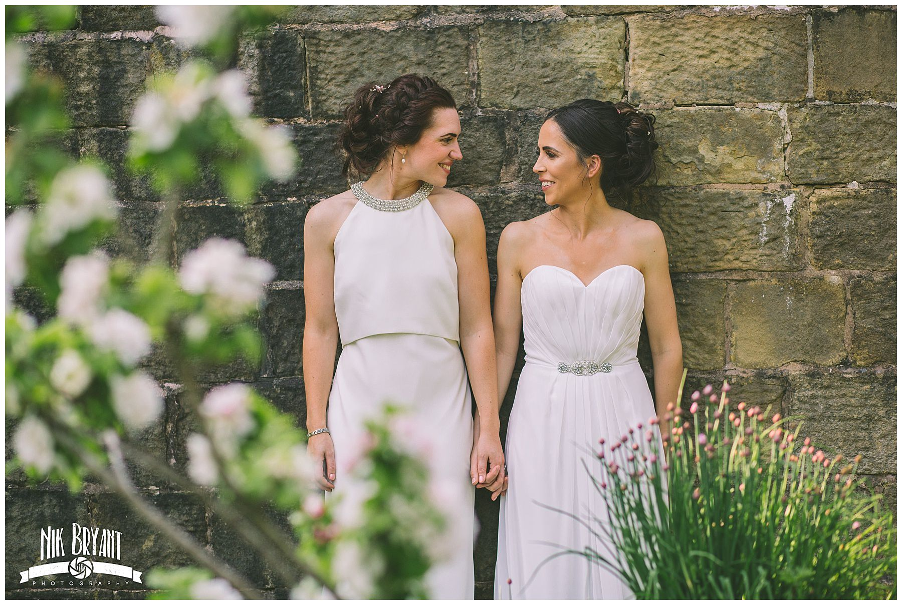 two brides stand hand in hand for couples portraits at Lancashire Wedding