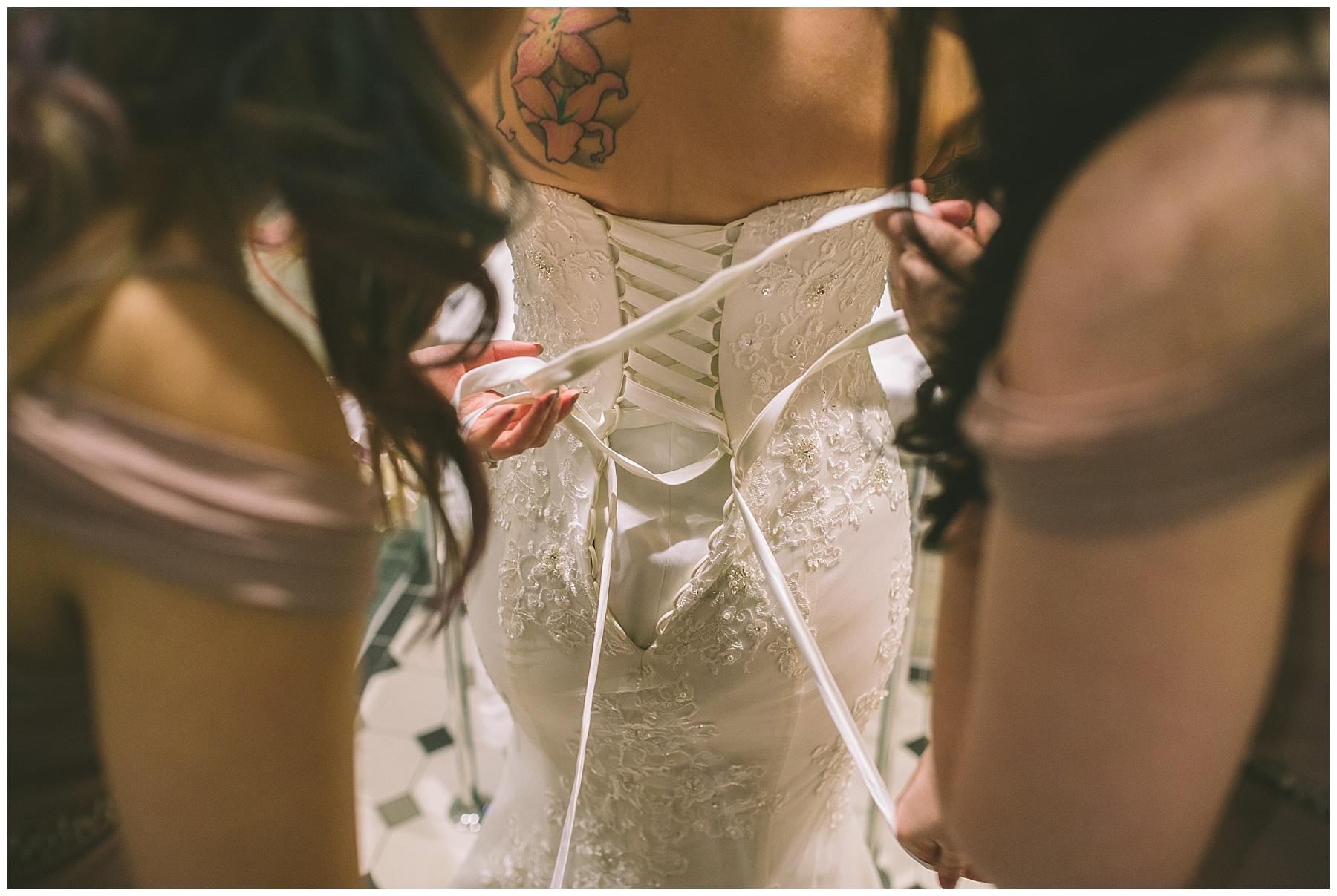 wedding dress being laced up by bridesmaids