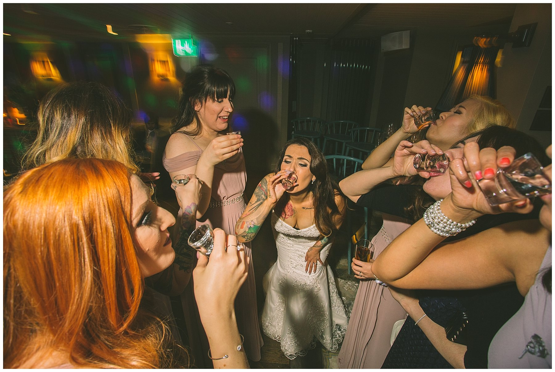 bride and bridesmaids do shots at winter wedding