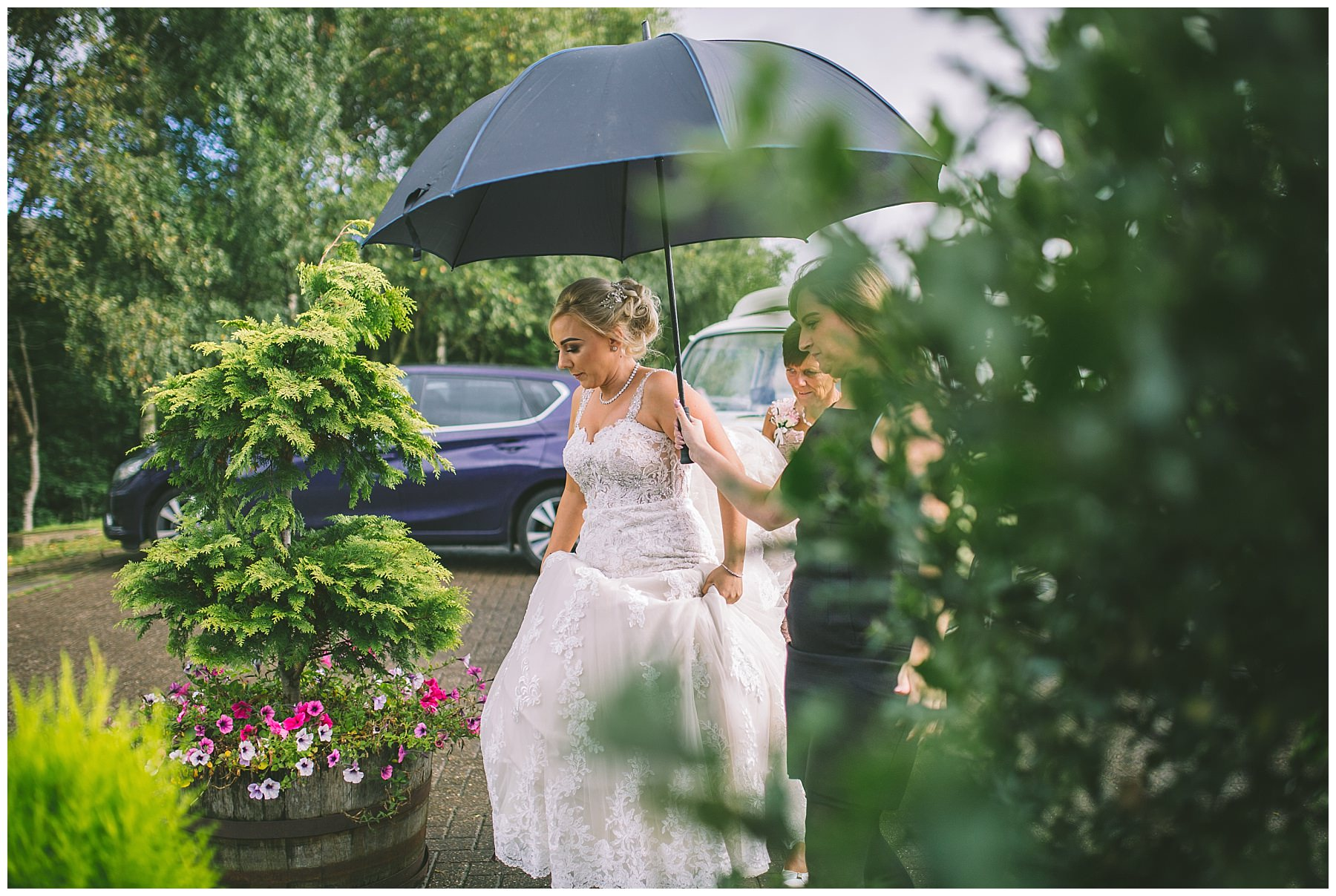 Bride arrives under an umbrella at the fishermans retreat