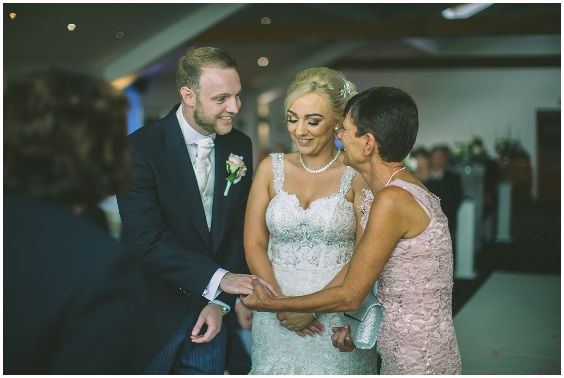 mother of the bride offers daughters hand to groom