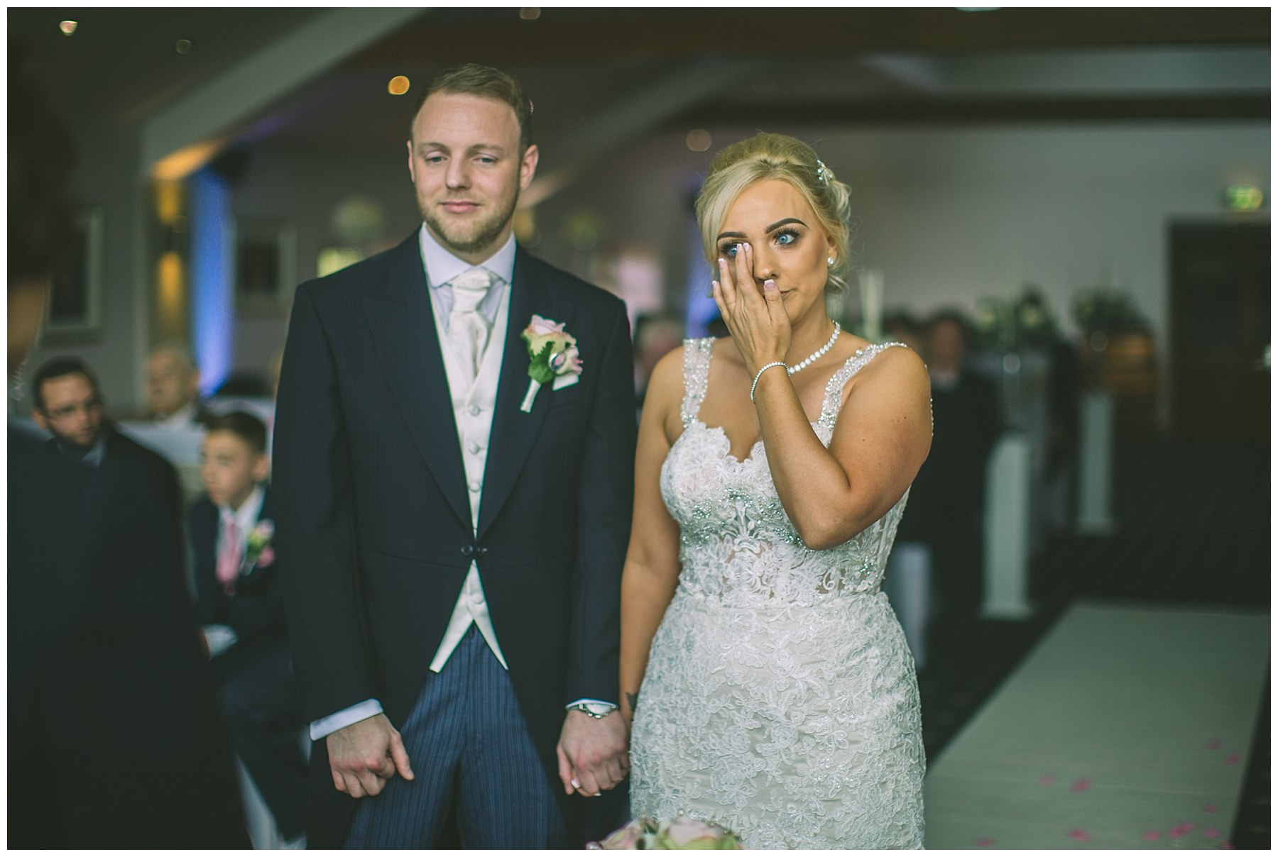 Bride wipes a tear from her eye during wedding ceremony