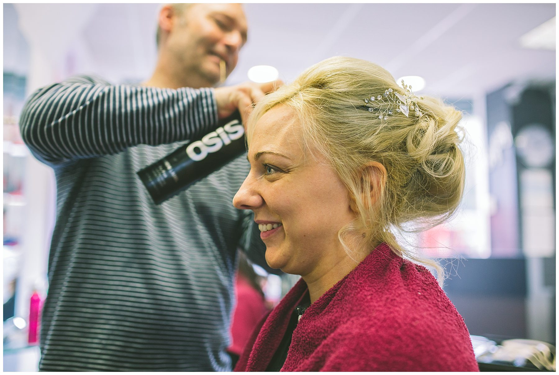 Bride smiles as she has her hair done on the morning of her wedding