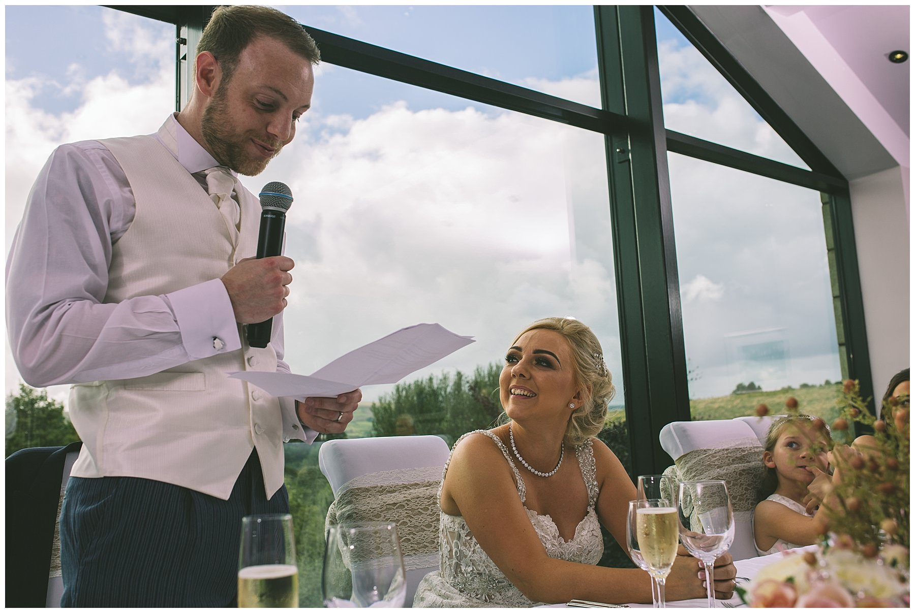 Bride looks at her new husband as he gives a speech
